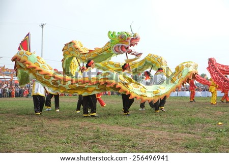 HANAM, VIETNAM - FEBRUARY 25: A group of unidentified  dancer with their colorful dragon during the traditional festival celebrations in the Tet Lunar New Year on Feb 25, 2015 in Ha Nam, Vietnam. - stock photo