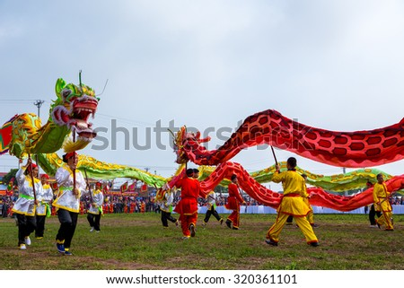 HANAM, VIETNAM - FEBRUARY 25, 2015: Dancers wearing traditional costumes dancing with the dragon in the Tich Dien festival in Hanam, Vietnam - stock photo