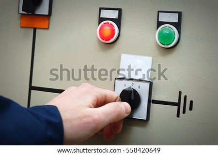 Hand a man in overalls includes an electric switch, two signal lights, red and green on the electrical panel.