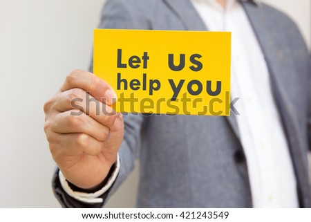 """hand action on business suit means business activities use for empower,encourage,work business, or present work, business, products, recruit with yellow card word """" let us help you"""" - stock photo"""