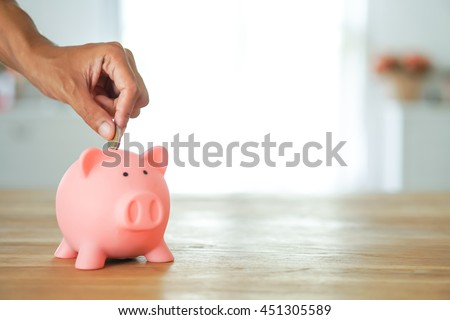 hand add coin to piggy bank save coin, time and money concept. copy space on right side. - stock photo