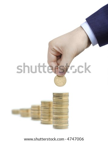 Hand adding coins against white background - stock photo