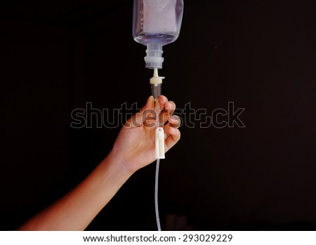 hand adjust an IV flow rate - stock photo