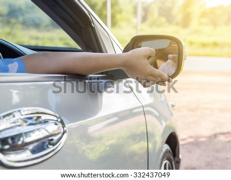 Hand adjusting side rear-view mirror. - stock photo