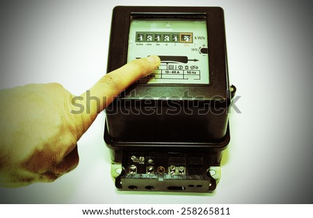 hand and a very old meter of electrical energy consumption with the number thirteen in display - stock photo