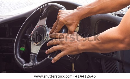 Hand and arm the driver holding the steering wheel in a car accident which damaged the glass cracking.