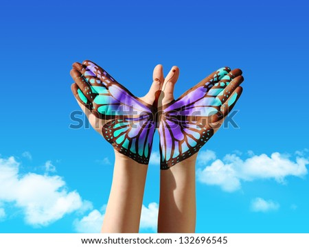 Hand and butterfly hand painting, tattoo, over a blue sky,  concept for spiritual symbol of soul - stock photo