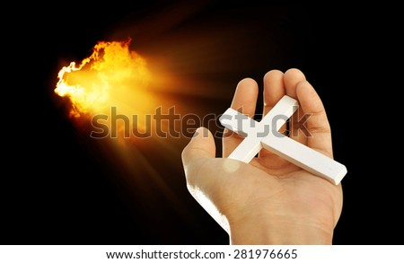 Hand and cross on light beams background , concept design - stock photo