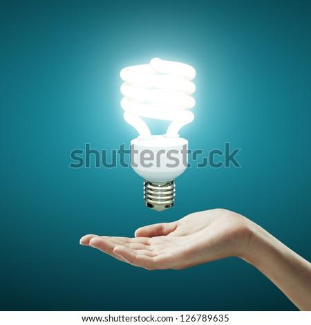 hand and energy saving lamp - stock photo