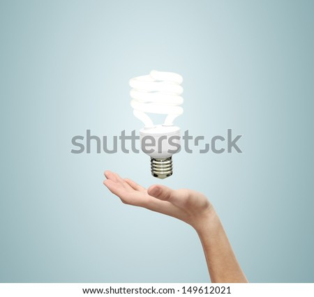 hand and energy saving lamp on a blue background