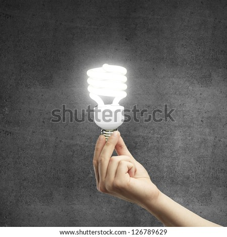 hand and energy saving lamp on gray background