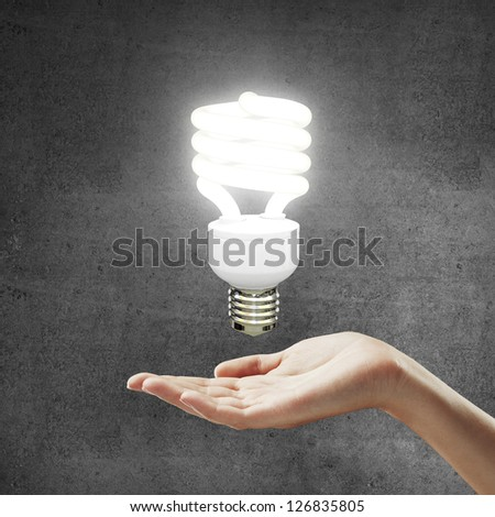 hand and energy saving lamp on gray background - stock photo