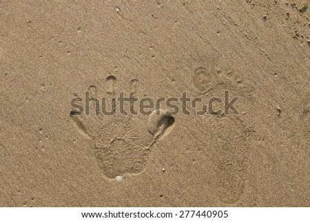 hand and foot prints on the sand at beach - stock photo