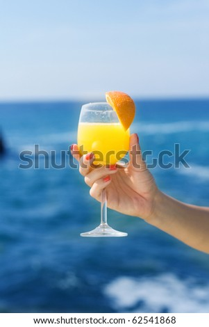 Hand and glass with orange juice - stock photo