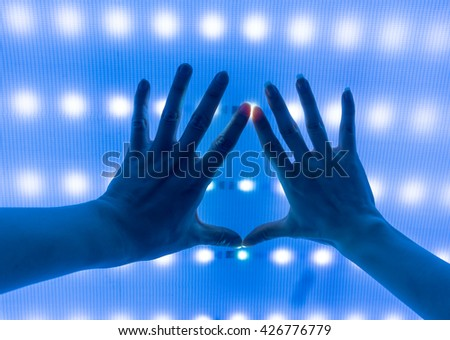 hand and led touch screen blue light science and technology background