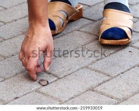 Hand and lost coin on footpath close up          - stock photo