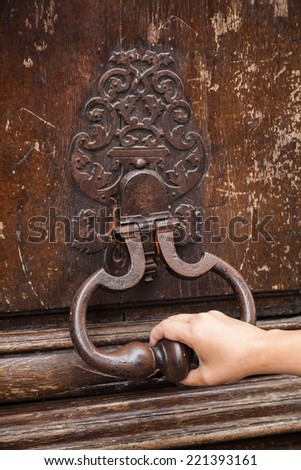 Hand and old rusted knocker on brown wooden door in Paris, France - stock photo
