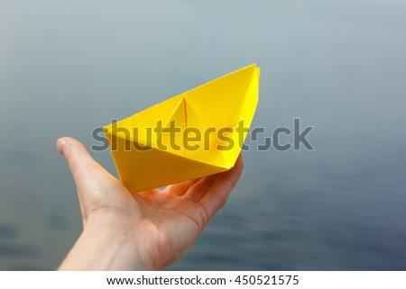 Hand and paper boat. Launching a ship - stock photo