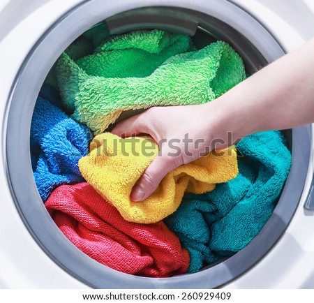 hand and puts the laundry into the washing machine. focus on a colored towel - stock photo