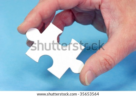 Hand and puzzle, isolated on blue background - stock photo