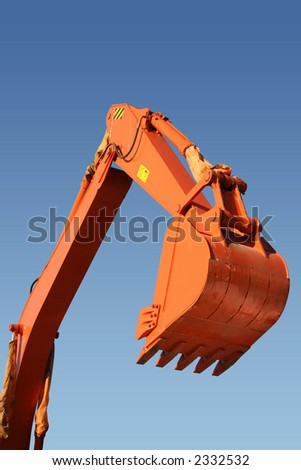 Hand and shovel bucket on a background of the blue sky, Isolated - stock photo
