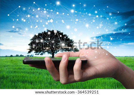 Hand and smartphone with single tree and city scape. Concept abstract idea of sharing nature and technology, technique retouch two image land scape and hand in studio.