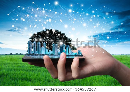 Hand and smartphone with single tree and city scape. Concept abstract idea of sharing nature and technology, technique retouch two image land scape and hand in studio.  - stock photo
