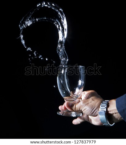 hand and splashing water on black background - stock photo