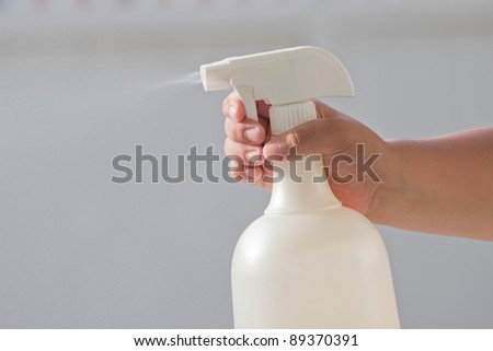hand and spray bottle on gray background