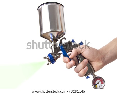 Hand and spray gun at work - stock photo