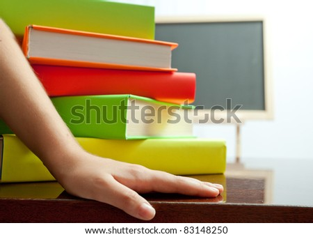 Hand and stack of colored book on the table - stock photo