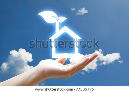 Hand and vivid eco houes icon on sky - stock photo