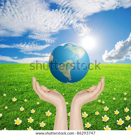 Hand and world in Grass fields and sun sky , photo of Earth from NASA - stock photo