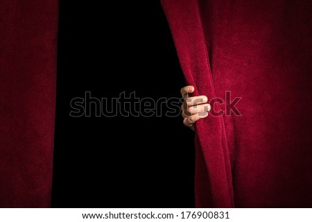 Hand appearing beneath the curtain. Red curtain. - stock photo