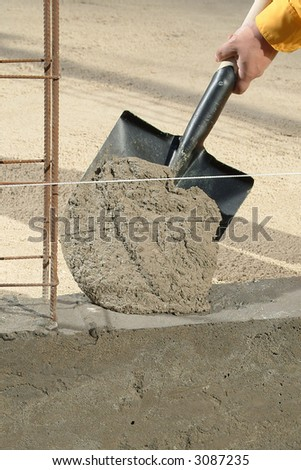 hand applying cement with a shovel on a wall in progress - stock photo