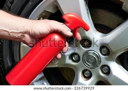Hand applying polish car wheel - stock photo