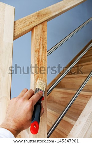 Hand applying protective oil on wooden stairs - stock photo