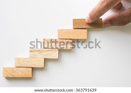 Hand aranging wood block stacking as step stair. Business concept for growth success process. - stock photo