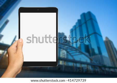 Hand are holding Small Tablet Computer with office building background - stock photo