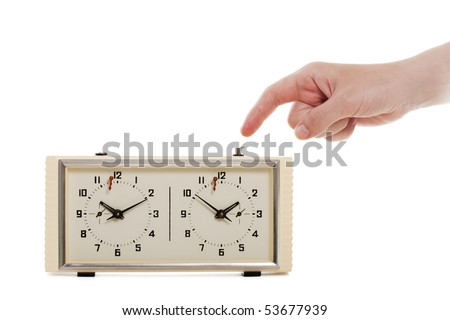 Hand arm pushing white chess sport game time clock - stock photo