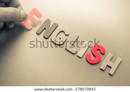 Hand arrange wood letters as English word - stock photo