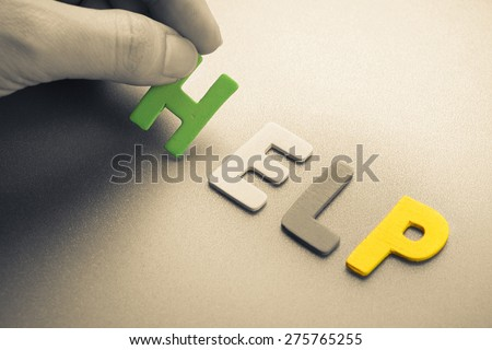 Hand arrange wood letters as Help word - stock photo