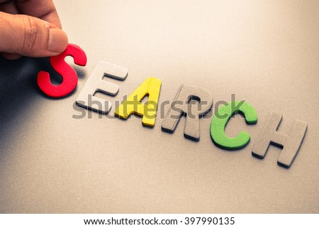 Hand arrange wood letters as Search word - stock photo