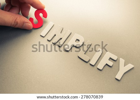 Hand arrange wood letters as Simplify word - stock photo
