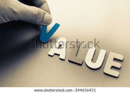 Hand arrange wood letters as Value word - stock photo