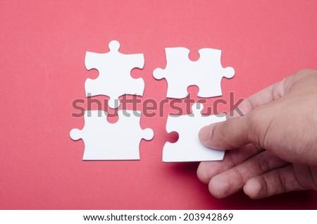 Hand arranging white puzzle - stock photo
