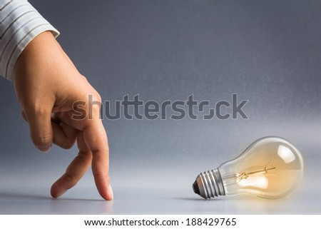 Hand as finger walking to the light bulb as idea symbol - stock photo