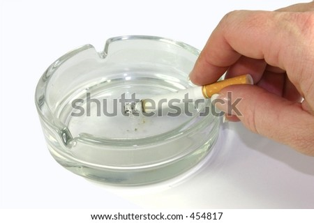 Hand ashing cigarette in ashtray - stock photo