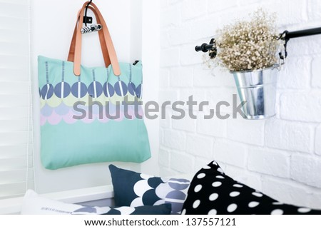 Hand bag hung on the white brick wall with colorful pillows - stock photo