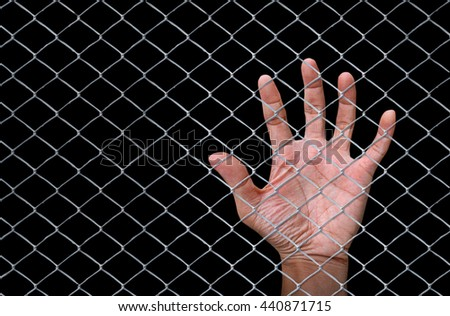 Hand behind a fence on a black background , imprisonment concept  , imprisonment , lack of freedom